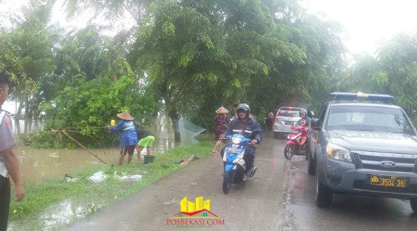 Debit air mulai naik dan hampir menyentuh bibir badan jalan di Desa Sukamekar, Kecamatan Sukawangi, Kabupaten Bekasi.[Trans]