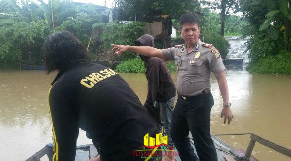 Kapolsek Tambelang, AKP Sujono, saat meninjau debit sungai yang membatasi Kecamatan Sukawangi dan Kecamatan Babelan.[Trans]