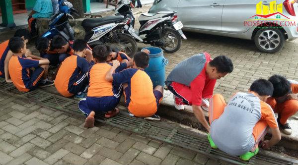 Aksi bersih lingkungan sekolah oleh siswa SDN Padurenan 1, Kecamatan Bantargebang, dipimpina langsung para guru, Minggu (21/2/2016).[Ida]