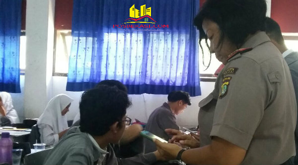 Kanit Binmas Iptu Desy Yulhasri saat memeriksa handphone siswa SMAN 1 Setu.[IDH]