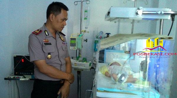 Kapolsek Setu AKP Agus Rohmat,SH, memperhatikan kondisi bayi yang dibuang kini mendapat perawatan di RS Kartika Husada Burangkeng Setu.[FER]