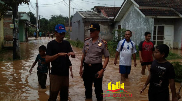 Kapolsek Setu AKP Agus Rohmat memantau banjir yang merendam ratusan rumah warga di Kecamatan Setu.[Idh]