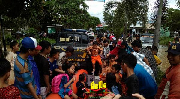 Anak-anak sekolah diangkut dengan perahu karet saat banjir melanda sebagian permukiman warga di Kecamatan Setu.[Idh]