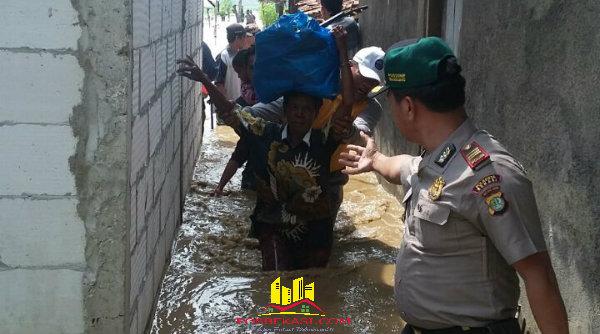 Kapolsek Tambelang AKP Sujono, tampak menyambut korban banjir yang dievakuasi akibat banjir melanda Desa Sukamekar, Sukawangi, Kabupaten Bekasi.[BES]