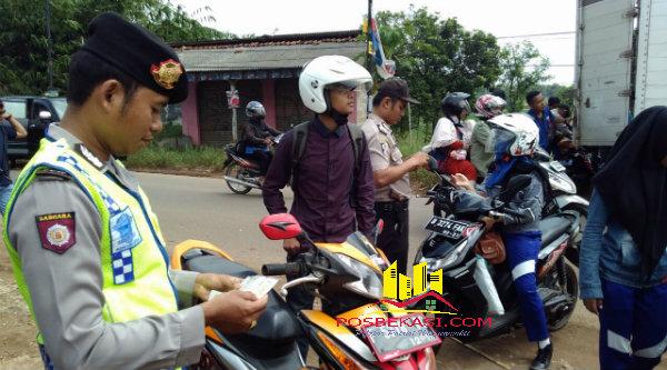 Petugas saat meneliti kelengkapan surat-surat pengdera kenderaan pada Operasi Cipkon diperbatasan Setu-Cileungsi, Bogor.[BES]