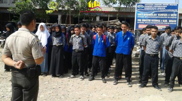 Anggota Binmas Polsek Setu, Bripka Nursalim, memberi pengarahan di SMK Industri di Desa Lubang Buaya.[IDH]