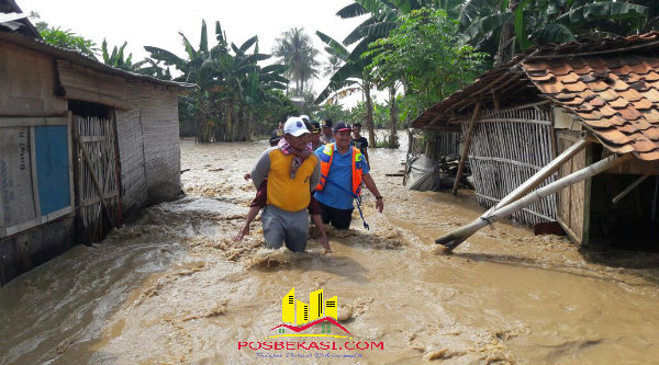 Kapolsek Tambelang AKP Sujono memimpin evakuasi korban banjir yang melanda Desa Sukamekar, Sukawangi, Kabupaten Bekasi.[BES]