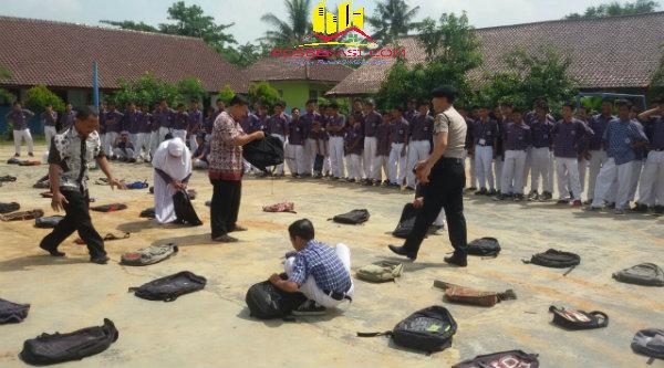 Brigadir Faisal Malis saat melakukan pemeriksan tas pelajar di bantu para guru sekolah.[FER]