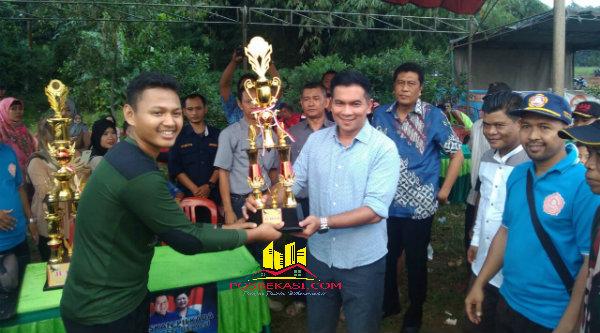 Krisna Mukti menyerahkan piala pada Tim Dustri Utama Cileungsi sebagai juara pertama piala Ragemanunggal Cup 2016 dilapangan bola Desa Ragemanungal Setu, Kabupaten Bekasi, Minggu (22/5/2016).[RAD]