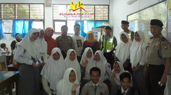 Anggota Polsek Setu yang melakukan pengamanan pengumuman hasil UN berfoto bersama dengan murid dan guru sekolah.[IDH]