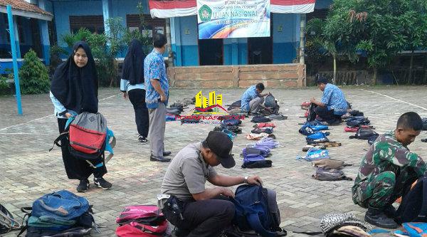 Bripka Nursalim dan Pelda Wawan dibantu para guru saat memeriksa tas para pelajar SMP yang mengikuti UN.[IDH]