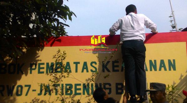 Walikota Bekasi, Rahmat Effendi, saat memanjat tembok pembatas wilayah Kelurahan Jatibening Baru, Kecamatan Pondok Gede.[IDH]