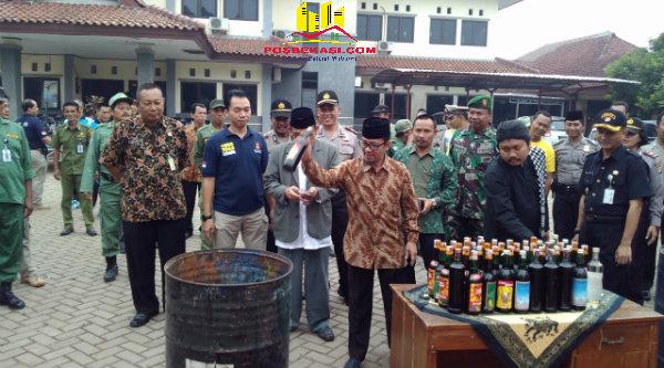 Ketua MUI Setu H.Abd Kadir Jaelani saat melakukan pemusnahan miras yang berhasil disita oleh Polsek Setu selama Operasi Pekat Jaya 2016.[YAN
