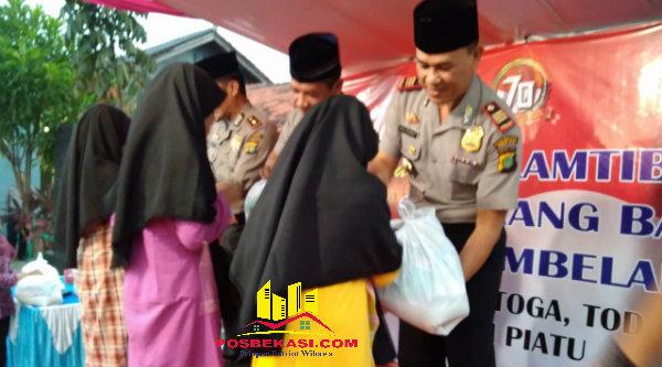 Kapolsek Setu, Kapolsek Cikarang Barat dan Kapolsek Tambelang, saat memberi santunan paket pada anak yatim dan piatu.[IDH]
