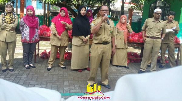 Kepala SDN Padurenan 1, Murtani Musyaini, saat menyalurkan zakat kepada 46 siswa dan 40 masyarakat sekitar sekolah, Selasa (21/6/2016).[HSB]