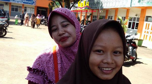 Seorang siswi dan ibunya saat meninggalkan sekolah setelah mengambil hasil UN MTsN Setu.[PRJ]
