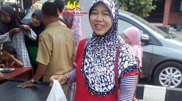 Seorang ibu membeli daging di pasar murah yang digelar di depan Kantor Camat Tarumajaya, Selasa (14/6/2016).[IDH]