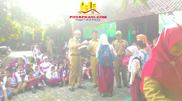 Guru Agama Rosyim, saat menyerahkan zakat kepada 46 siswa SDN Padurenan 1, Selasa (21/6/2016).[HSB]