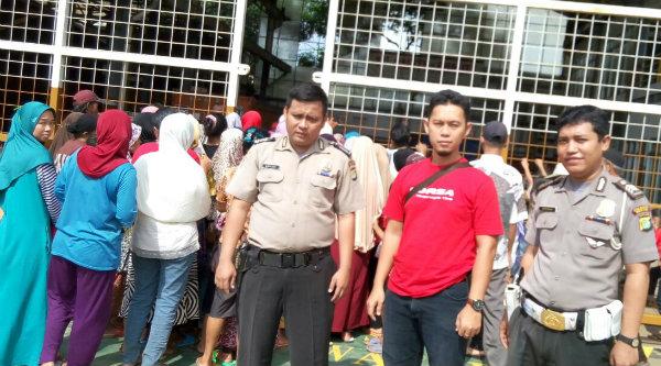 Bripka Deri Luvi memberi pengamanan pada masyarakat yang antri sebako dan zakat yang dibagikan oleh PT Gearindo Prakarsa.[RAD]