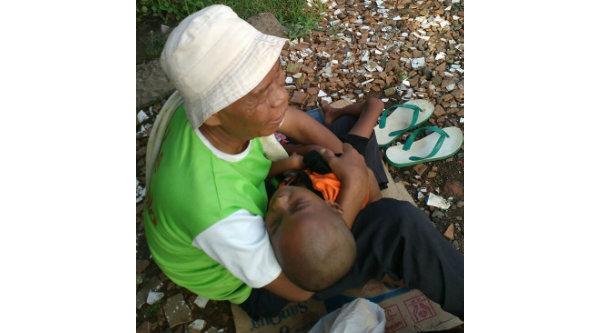 Gepeng Ateng memangku anaknya yang mengalami gizi buruk setiap hari mengemis di pinggir rel kereta api Tambun.[HSB]