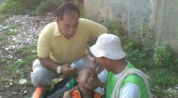 Kasi Humas Polsek Tambun, Iptu Trimulyono bersama gepeng Ateng memangku anaknya yang mengalami gizi buruk.[HSB]