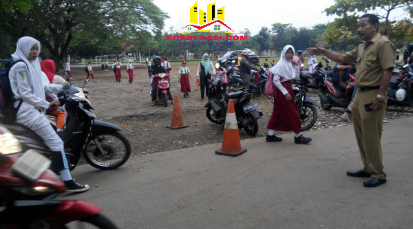 Kepsek SDN Padurenan 1, Jomin Jamaludin, setiap pagi turun ke lapangan mengatur parkir kenderaan orangtua yang mengantar anak ke sekolah demi kelancaran lalu lintas.[SOF]