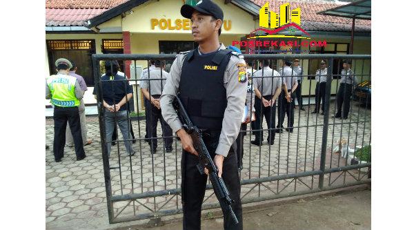 Anggota Polsel Setu dilengkapi dengan senjata laras panjang saat  berjaga di gerbang Mapolsek guna mengantisipasi serangan teroris.[YAN]