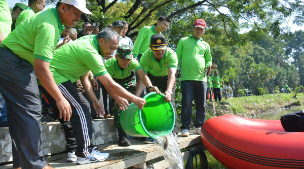 Wakil Walikota Bekasi, Ahmad Syaikhu, menebaran benih ikan mas dan mujair di telaga Taman Duta Harapan Baru yang biasa dikenal sebagai Telaga Mas.[IDH]