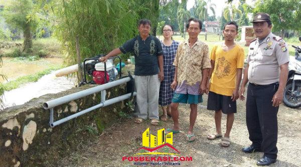 Kapol Sub Sektor Griya Pratama Mas (GPM), Polsek Setu, Aiptu Edison Sitorus, bersama warga GPM melakukan penyedotan air yang menggenangi badan jalan perumahan tersebut, Senin (8/8/2016).[IDH]