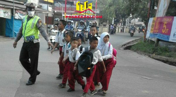 Bripka Budi Sauri saat menuntut anak sekolah untuk menyeberang jalan.[IMA]