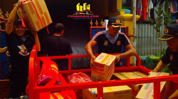Anggota Pokdar Kamtibmas Polsek Metro Setu saat mengangkut sumbangan warga yang dikumpul di Posko sementara di Perumahan Bekasi Timur Regensi.[IDH]