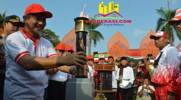 Wakil Walikota Bekasi H Ahmad Syaikhu memegang Api PON XIX Jabar yang tiba di Kota Bekasi pada Sabtu, 10 September 2016, sore.[ISH]