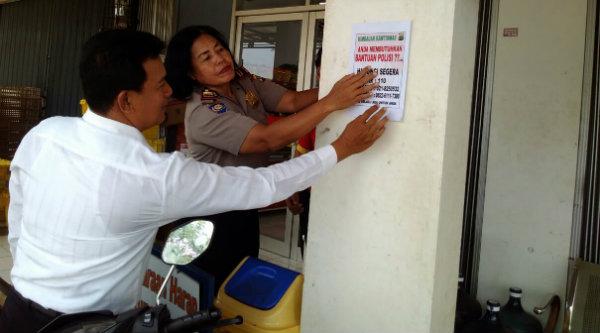 Kanit Binmas Setu Iptu Desy Yulhasri bersama Kanit Intelkam Aiptu Suroso memasng stiker pengaduan masyarakat,[RAD]