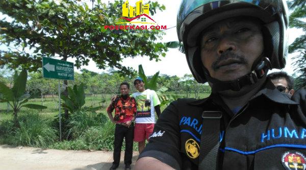 Kasi Humas Polsek Setu Aiptu Parjiman memantau jalur peserta Fun Bike Kertarahayu yang melalui kawasan perkebunan dan pematang sawah.[SOF]