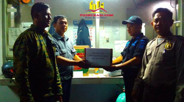 Tampak Camat Setu Adeng Hudaya mengantarkan bantuan korban bencana alam Garut kepada Ketua Pokdar Kamtibmas di Posko Bantuan Mapolsek Metro Setu, Riki.[IDH]