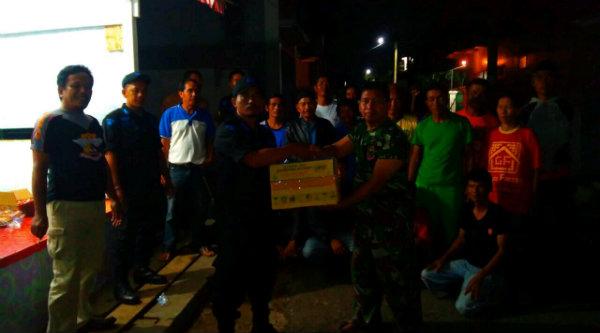 Disaksikan warga Kampung Cigandil yang terkena musibah bencana alam, Ketua Pokdar Polsek Metro Setu, Riki, menyampaikan bantuan masyarakat Bekasi untuk korban bencana kepada  Kaptain Furqon.[RIK]