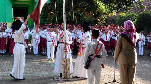 Tiga siswi bertugas mengibarkan bendera Merah Ptutih.[IMA]