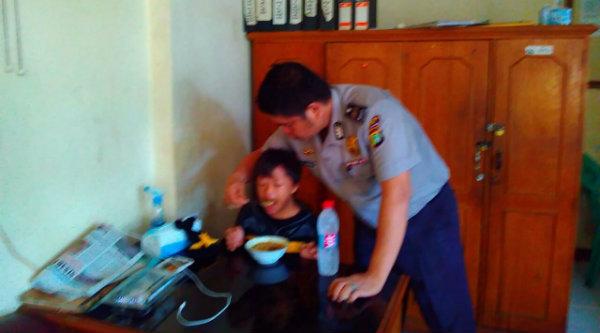 Aiptu CT Siagian KSPKT Polsek Metro Setu saat memberi makan anak hilang yang diamankan di Mapolsek.[RAD]