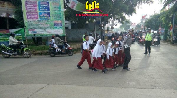 Kanit lantas Polsek Metro Setu, Ipda Herry Setiawan, saat menyeberangkan anak-anak SD untuk berangkat sekolah.[IMA]