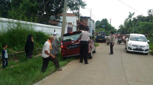 Anggota Polsek Setu menolong kenderaan yang terperosok keluar badan jalan.[RIN]