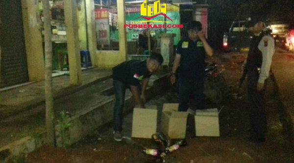 Polisi memusnahkan miras dengan cara memecah botol didepan toko jamu.[ZAI]