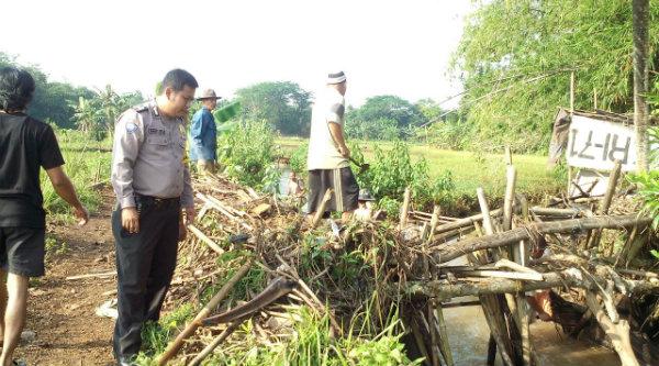 Bhabinkamtibmas Desa Tamansari, Bripka Deri Luvi bersama warga membersihkan Kali Cisadang.[RAD]