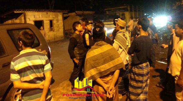 Aparat kepolisian Polsek Setu dan Pokdar Kamtibmas saat menenangkan massa yang menghakimi pelaku pencurian televise.[IDH]