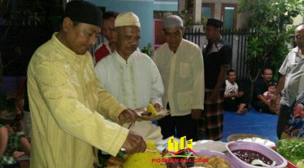 Ketua 007 BTR Parjiman memberikan potongan tumpeng pada tokoh masyarakat H Cahyadi, di acara doa keselamatan untuk warga dan Indonesia, Sabtu 19 Nopember 2016.[RAD]