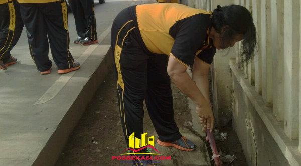 Kanit Binmas Iptu Desy Yulhasri saat membersihkan got depan Mapolsek Setu.[RAD]
