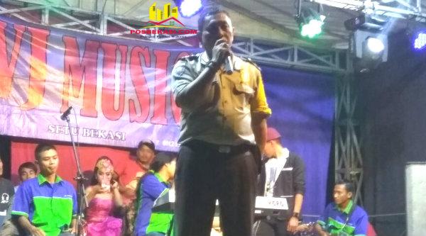 Binmaspol Desa Desa Ketarahayu, Aiptu Yulianto, menyampaikan pesan Kamtibmas pada acara saweran dangdut di Kampung Cisaat.[OJI]