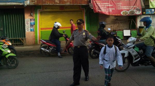 Setiap pagi hari Kanit Patroli Polsek Setu, Iptu Herunanto, menuntun anak-anak menyeberangi jalan untuk berangkat ke sekolah.[PRJ]