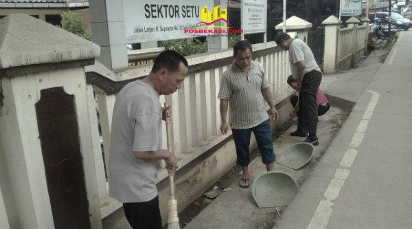 Anggota Polsek Setu membersihkan saluran air hingga ke jalan di depan Mako pada Sabsih pagi.[HSB]