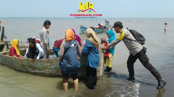 Binmaspol Pantai Bahagia Bripka Wahyudin membantu perahu yang akan membawa wisatawan kembali setelah liburan di Pantai Beting.[SUB]