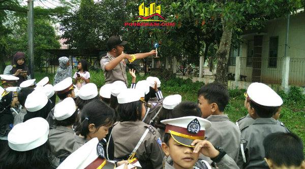 Binmaspol Desa Burangkeng, Aipda Hari Cahyono mempraktekan disipilin berlalulintas pada anak-anak TK Albhana.[RAD]